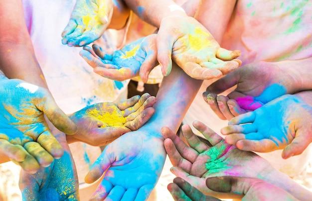 Il mazzo di mani variopinte del gruppo degli amici che si diverte alla spiaggia fa festa sulle vacanze estive di festival di colore di holi