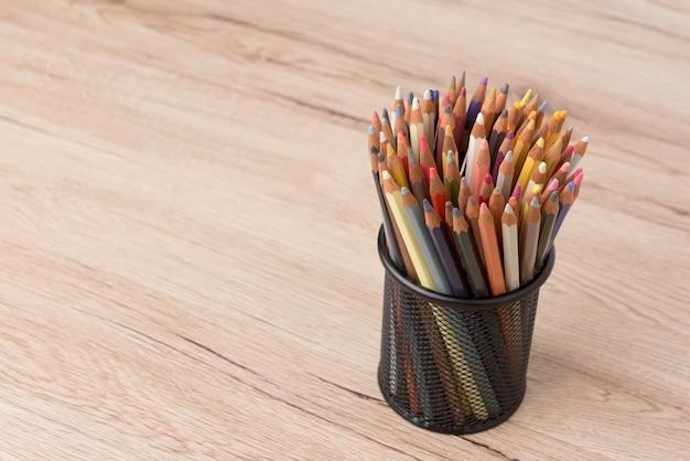 Il mazzo di matite colorate nel barattolo ha messo sopra la tavola di legno.