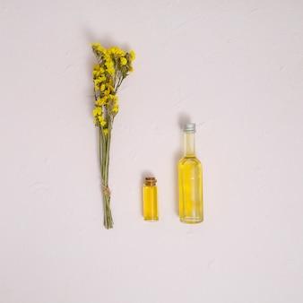 Il mazzo giallo del limonium fiorisce con le bottiglie di olio essenziale sul contesto concreto bianco