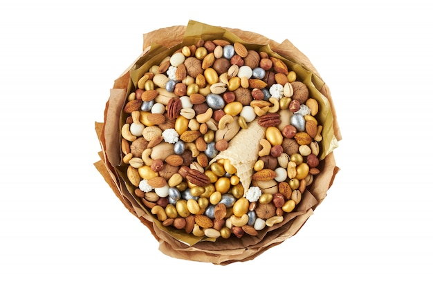 Il mazzo ha creato dalle noci dei gradi e delle caramelle differenti, vista superiore su bianco