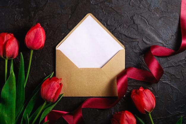 Il mazzo rosso di tulipano fiorisce con la carta della busta e nastro sulla superficie del nero, spazio della copia di vista superiore