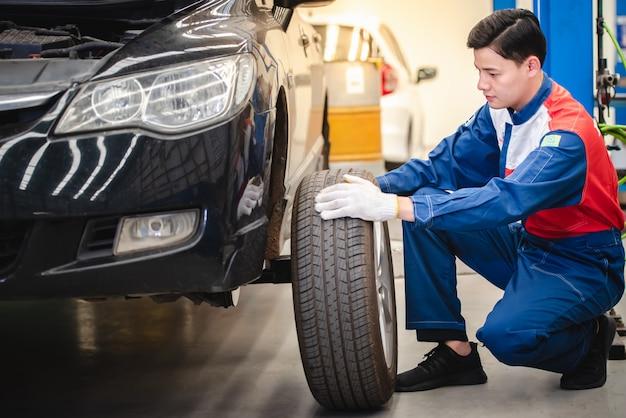 Il meccanico asiatico sta rimuovendo la ruota e controllando i freni e le sospensioni nel servizio auto con un carrello elevatore. centro di riparazione e manutenzione