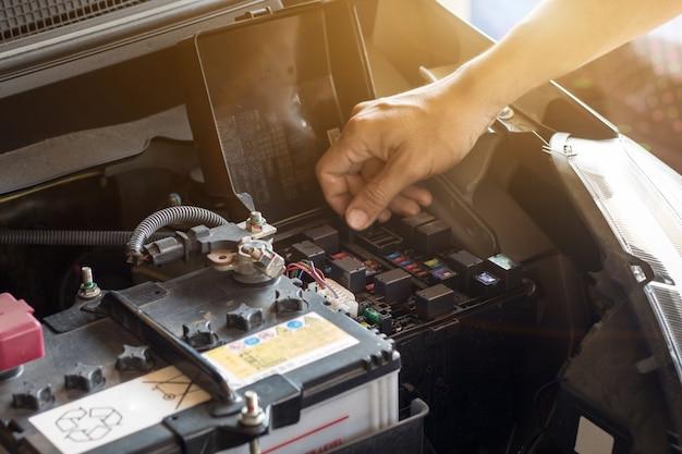 Il meccanico che lavora controlla l'acqua del sistema e riempie un vecchio motore dell'automobile alla stazione di servizio, cambia e ripara prima di guidare