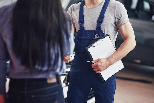 Il meccanico del marito e la donna cliente fanno un accordo sulla riparazione della macchina