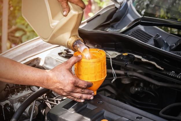 Il meccanico dell'auto aggiunge olio al motore, all'industria automobilistica e ai concetti di garage.