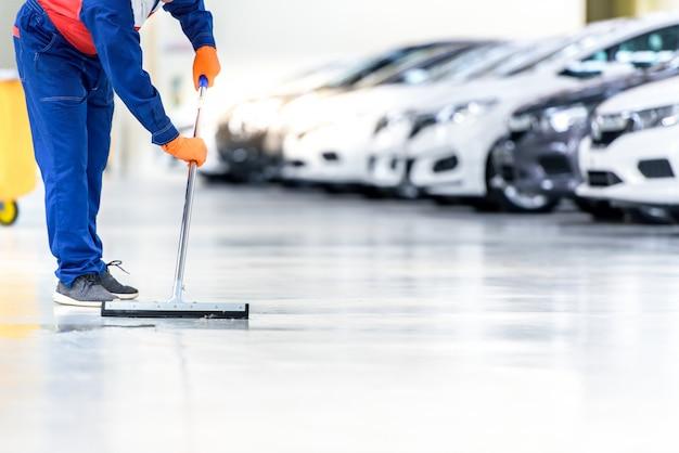 Il meccanico dell'auto sta pulendo, usando una scopa, rotolando l'acqua dal pavimento epossidico. nel centro di riparazione del servizio auto