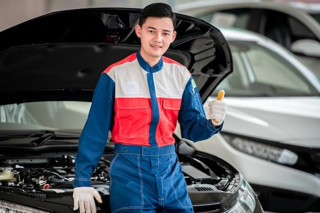Il meccanico di automobile asiatico in un'officina riparazioni automatica sta controllando il motore. per i clienti che usano le auto per i servizi di riparazione, il meccanico lavorerà in garage.