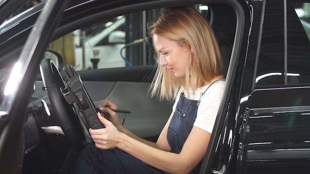 Il meccanico di automobile femminile lavora nella sua officina riparazioni automatica. un'opera preferita, un modo di vivere