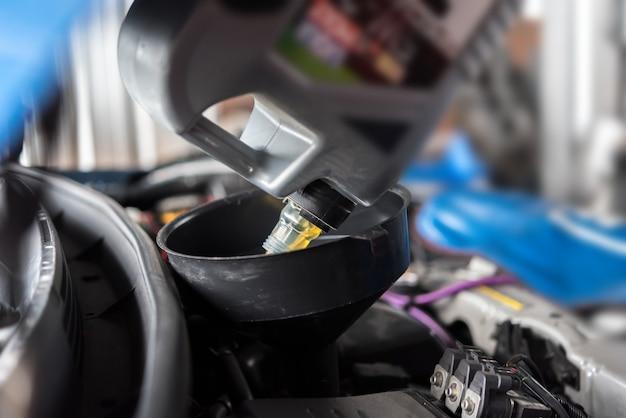 Il meccanico di automobile riempie un olio lubrificante fresco del motore