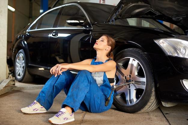 Il meccanico femminile si gode la pausa vicino all'auto dopo averla riparata