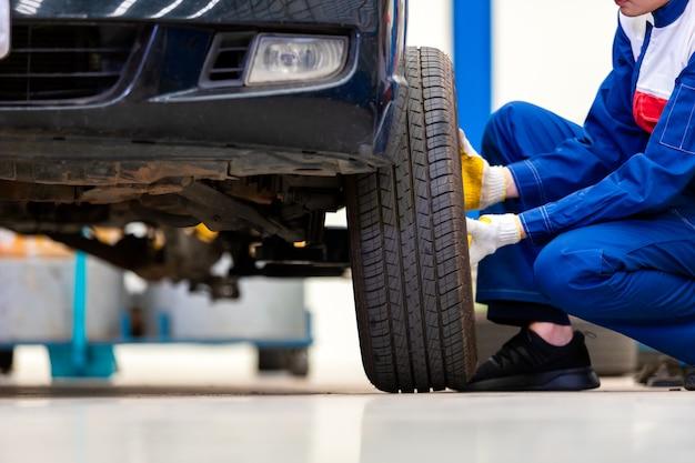 Il meccanico in uniforme sta cambiando ruote / pneumatici mentre lavora nel centro di riparazione auto