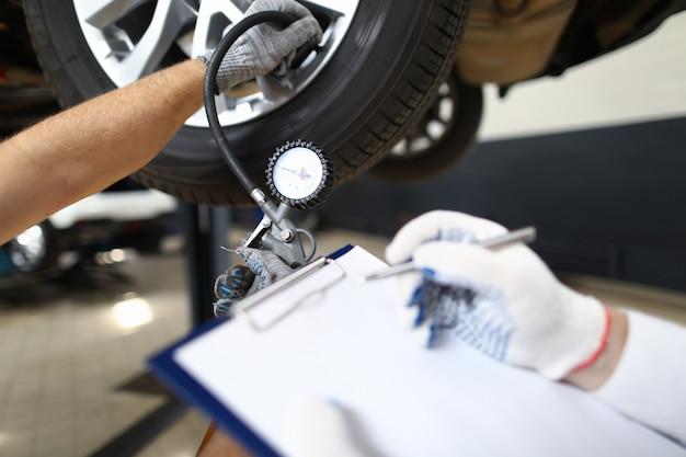 Il meccanico ispeziona un veicolo pre-vendita contro