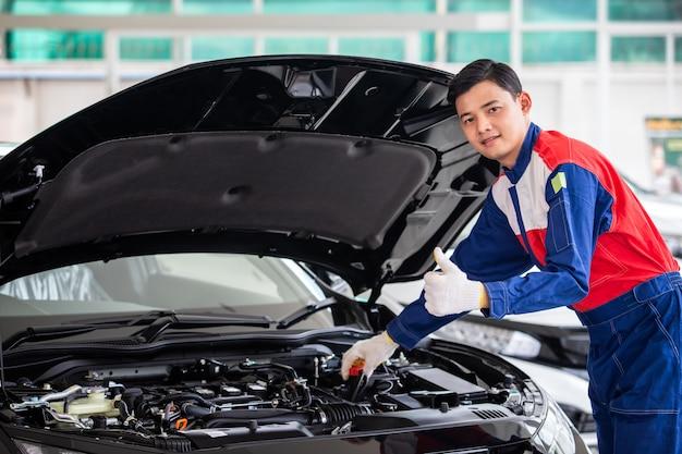 Il meccanico professionista in uniforme è controllare la qualità della nuova auto prima di consegnarla ai clienti. mentre si lavora nel centro di riparazione auto.
