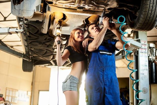 Il meccanico ripara un'auto sollevata in un servizio automobilistico