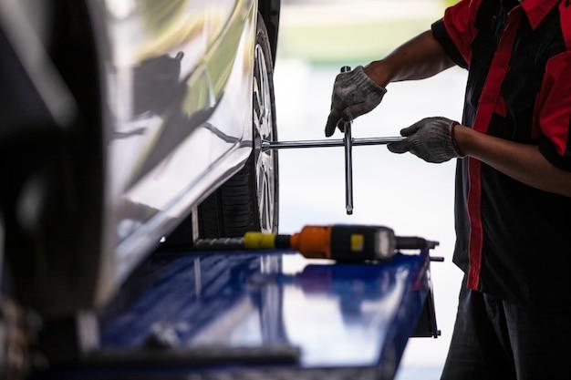 Il meccanico sta cambiando i pneumatici della vettura per chi usa il centro degli pneumatici.