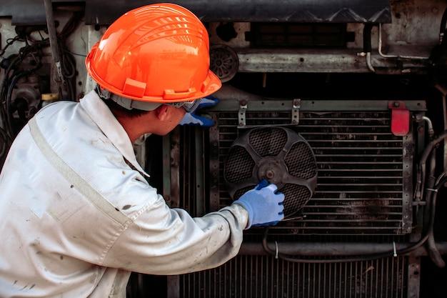 Il meccanico sta controllando la ventola del radiatore. di grandi motori per camion