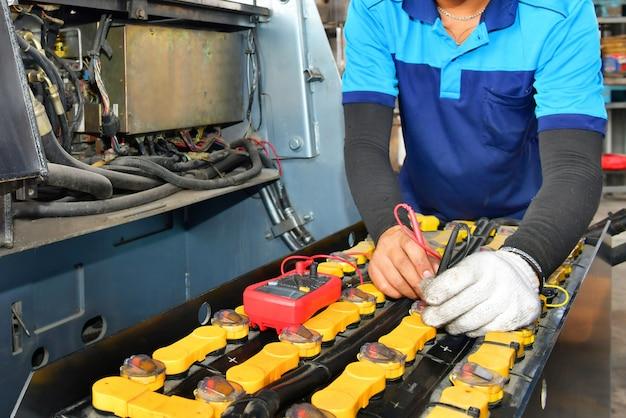 Il meccanico sta verificando la qualità del carrello elevatore voltmetro del tester di capacità della batteria per la manutenzione di servizio di riparazione industriale a motore