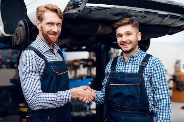 Il meccanico stringe la mano allo studente, grazie per l'ottimo lavoro.