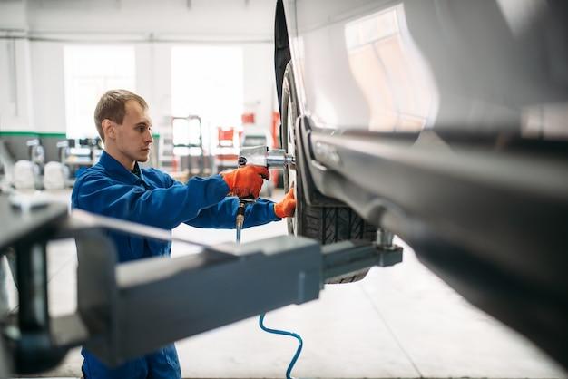 Il meccanico svita la ruota con chiave pneumatica