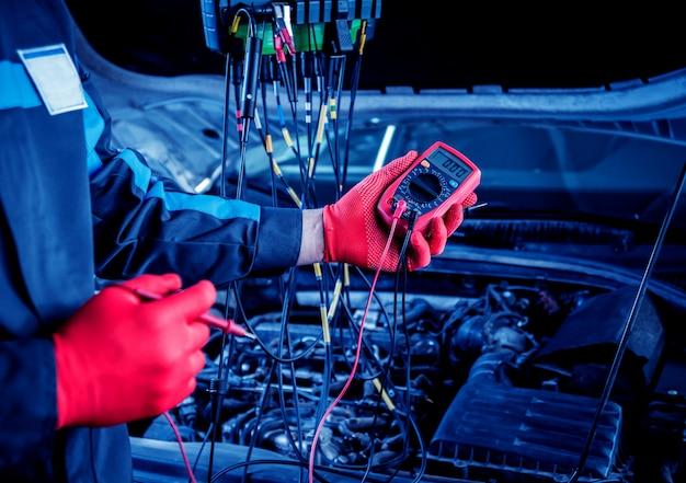 Il meccanico usa un voltmetro per controllare il livello di tensione.