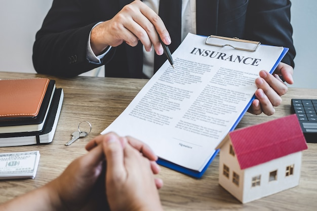 Il mediatore dell'agente immobiliare raggiunge il modulo di contratto con il cliente che firma il contratto di contratto immobiliare con modulo di richiesta di mutuo approvato, acquisto o offerta di prestito ipotecario e assicurazione casa