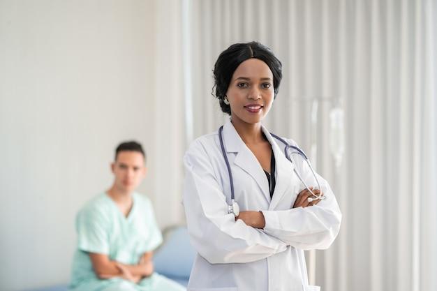 Il medico afroamericano sta controllando i sintomi controllando il cuore del paziente sul letto del paziente. e fornire consulenza in merito al trattamento per i pazienti seduti