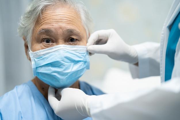 Il medico aiuta il paziente asiatico senior della donna che indossa una maschera in ospedale per proteggere il virus covid-19.