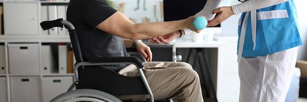 Il medico aiuta l'uomo sulla sedia a rotelle tenere il manubrio