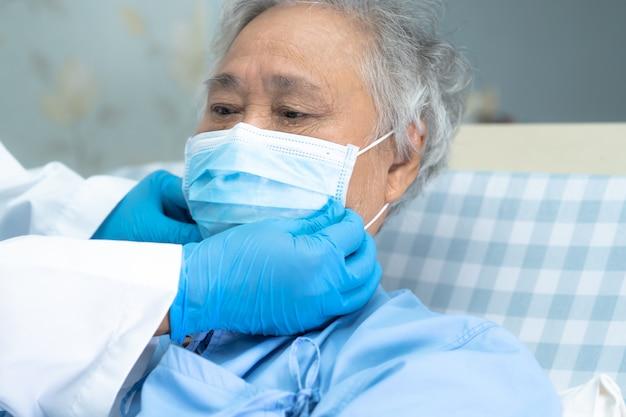 Il medico aiuta la signora senior che indossa una maschera in ospedale per proteggere le infezioni