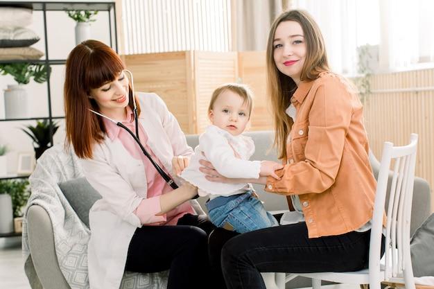 Il medico amichevole del pediatra della giovane donna parla con la madre di piccola neonata dopo l'esame