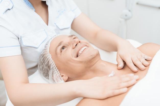 Il medico applica una crema curativa sul petto e sulle spalle dell'uomo.