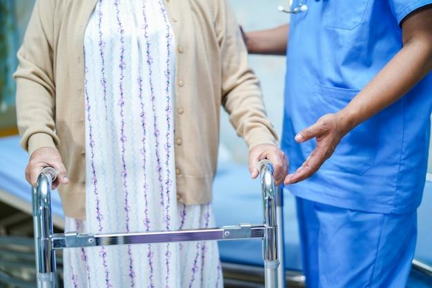 Il medico asiatico del fisioterapista dell'infermiere cura, aiuta e sostiene il paziente anziano della donna anziana con w