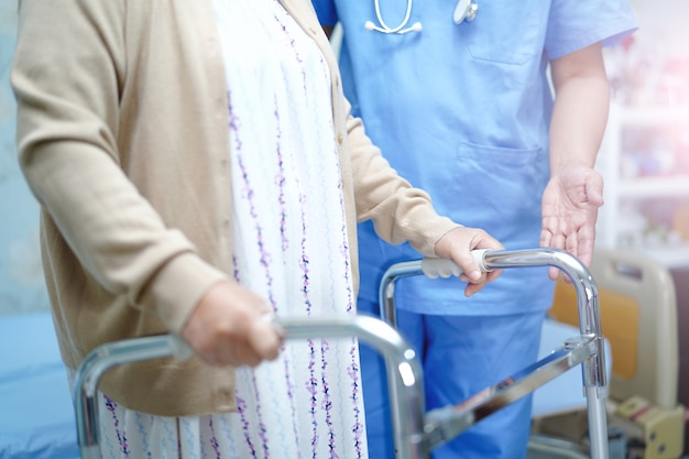 Il medico asiatico del fisioterapista dell'infermiere cura, aiuta e sostiene il paziente anziano della donna anziana.
