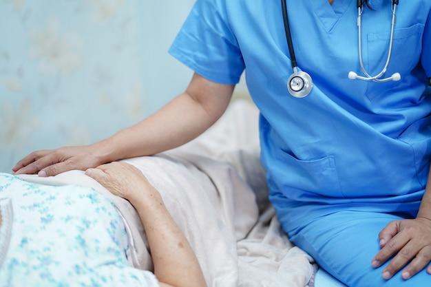 Il medico asiatico del fisioterapista dell'infermiere cura, aiuta e sostiene l'anziano