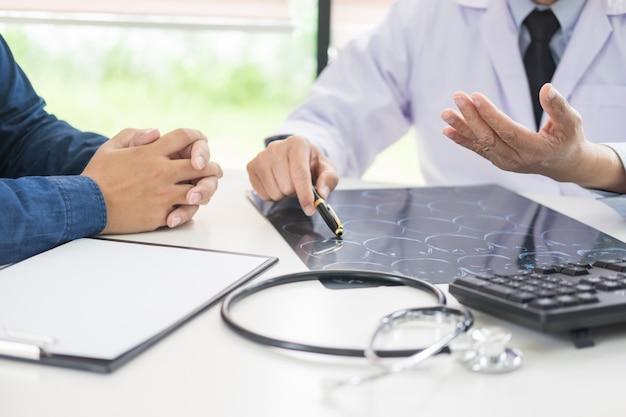 Il medico che analizza una scansione o un film a raggi x spiega una scansione tc che parla al cervello del paziente