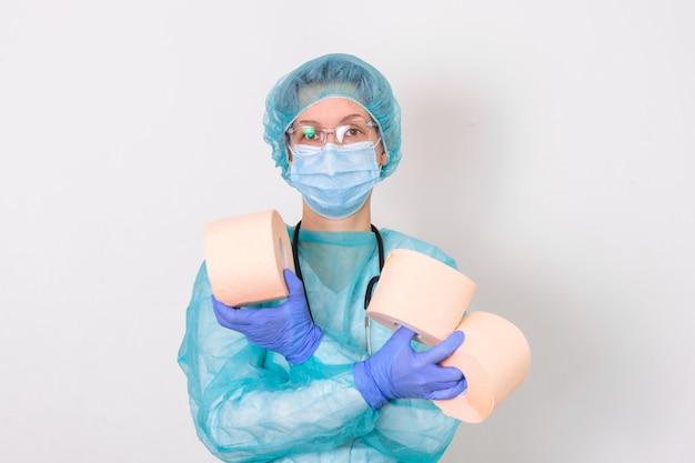 Il medico che indossa la suite di protezione dpi o l'infermiera con uno stetoscopio detiene un rotolo di carta igienica. mancanza di carta igienica nella quarantena del coronavirus, il concetto di carenza di cose nei negozi