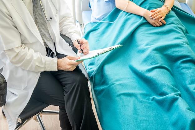 Il medico controlla e discute con il paziente in clinica o il medico parla con le donne pazienti in ospedale