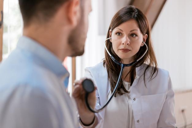 Il medico controlla il paziente con lo stetoscopio