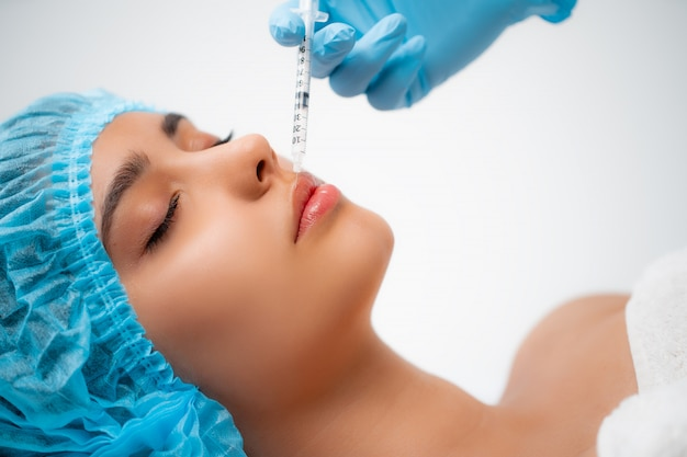 Il medico cosmetologo esegue la procedura di iniezioni facciali ringiovanenti per stringere e levigare le rughe sulla pelle del viso di una donna in un salone di bellezza. cosmetologia per la cura della pelle