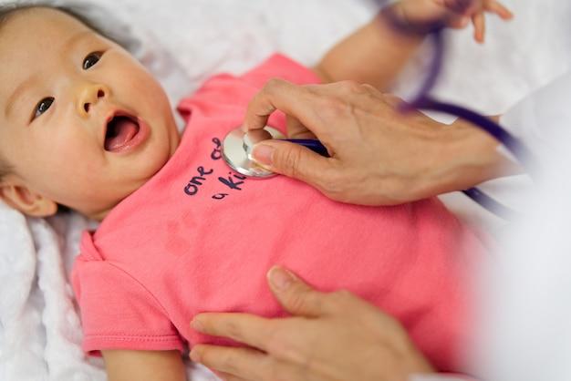 Il medico del bambino sta ascoltando la frequenza cardiaca del polso del neonato sveglio che si trova sul letto usando lo stetoscopio.