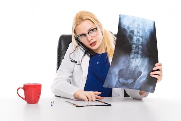 Il medico della donna in camice studia attentamente i raggi x