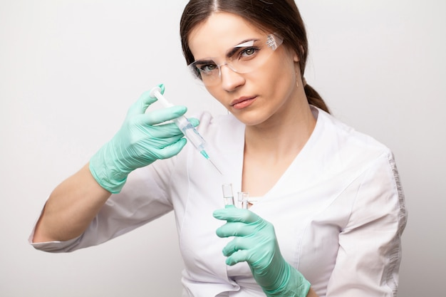 Il medico della donna nella mascherina medica preleva la siringa per fare un'iniezione.