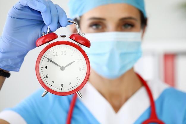 Il medico della donna nella mascherina medica protettiva tiene una sveglia