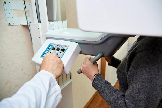 Il medico della mano in camice bianco preme i pulsanti di controllo