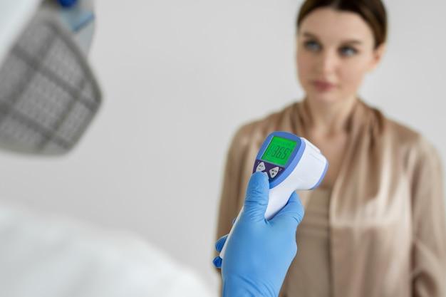 Il medico delle malattie infettive misura la temperatura di una paziente con un termometro a infrarossi in una clinica durante l'epidemia di coronavirus. covid-19