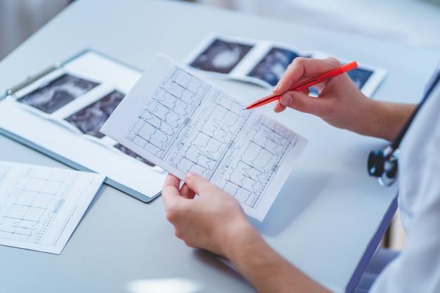 Il medico di famiglia esamina l'elettrocardiogramma del paziente durante un controllo sanitario e una consultazione medica