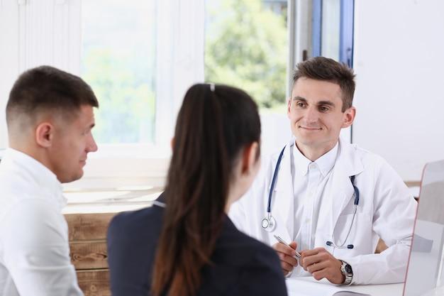 Il medico di famiglia maschio ascolta attentamente le giovani coppie in ritratto dell'ufficio.