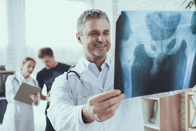 Il medico di sorriso sta esaminando i raggi x per l'atleta