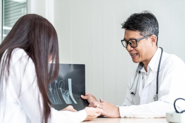 Il medico e il paziente asiatici stanno discutendo