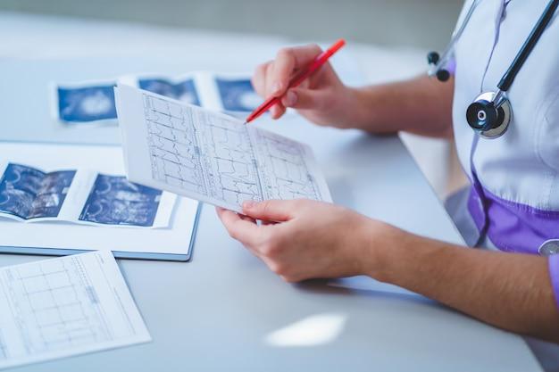 Il medico esamina l'elettrocardiogramma del paziente durante un controllo sanitario e una visita medica. diagnosi e trattamento della malattia